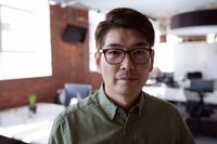 Portrait of serious asian businessman standing in office looking to camera