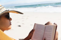 Mixed race woman on beach holiday wearing sunglasses reading book