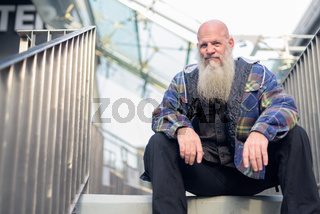 Mature bald hipster man with long beard sitting at footbridge in the city
