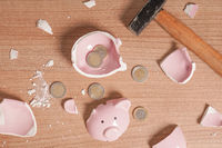 broken Piggy bank smashed into pieces with hammer and small chan