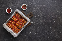 Roasted pork ribs in foil in metal baking dish. American food concept. Top view, copy space