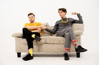 Two cute guys make a bet hand in hand sitting on a white sofa. Group of friends are sitting on a soft couch and communicates isolated on white background