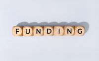 Funding word on wooden block isolated on gray background