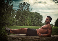 Muscular young man exercising in nature doing abs routine