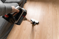 Cleaning wooden floor with wireless vacuum cleaner. Handheld cordless cleaner. Household appliance. Housework modern equipment
