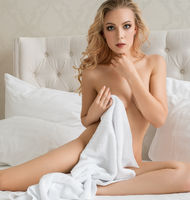Nude blonde with long locks in luxurious bed