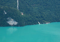 Giessbach Falls and historic hotel. Ship waiting at the shore of turquoise Lake Brienz.