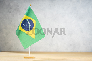 Brazil table flag on white textured wall. Copy space for text, designs or drawings