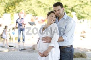 Schwangerschaft: Glückliches Paar im Park lächelt