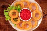 Squid rings close-up on a wooden background. Deep fried calamari rings