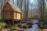 Beautiful log cabins by a stream in the forest and footbridge over the water