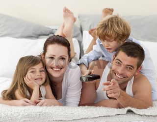 Family relaxing in bed and using a remote