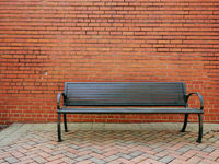 An empty park bench in front of a blank brick wall