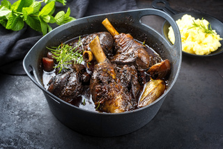 Modern style traditional braised slow cooked lamb shank in red wine sauce with shallots and mashed potatoes offered as close-up in a design stewpot