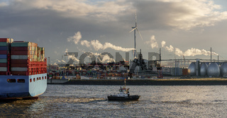 Container terminal in the port of Hamburg with tugboat and container ship in the foreground