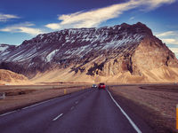 Car riding towards mountains in Iceland in winter