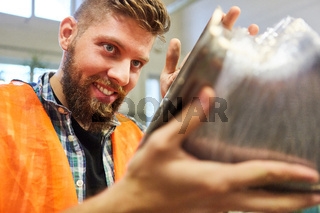 Metallarbeiter mit Produkt bei der Qualitätskontrolle