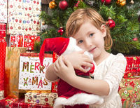 Kind vor Weihnachtsbaum mit Weihnachtsmann Spielzeug