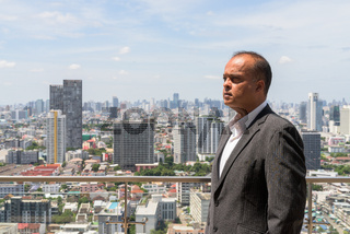 Profile view portrait of Indian businessman in city at Bangkok, Thailand