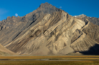 Zanskar Mountains cliff with clearly visible sediment rock layers, Rangdum Gompa and the rising moon