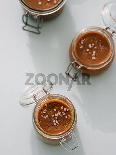 Salted caramel in glass jars, top view. Vertical