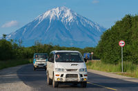 Japanese minivan Mitsubishi Delica driving on asphalt road on background travel destinations landscape