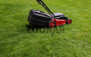 Electric mower over green grass lawn