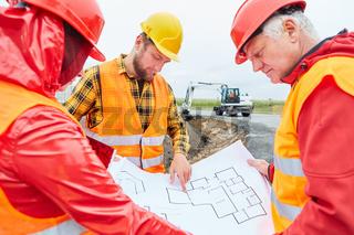 Bauarbeiter besprechen Bauplan vom Hausbau