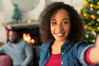 Happy african american woman taking selfie, christmas decorations in background
