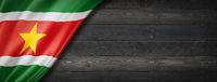 Suriname flag on black wood wall banner