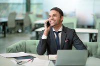Handsome man in business suit talking on the phone working on laptop, job in progress. Cheer smiling freelancer making notes in scheduler sitting in bright coworking space