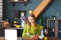 Woman cooking vegetable salad near laptop