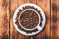 White cup full of roasted coffee beans