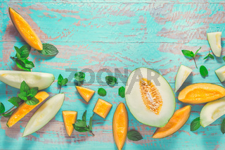 Healthy snack - Piel de sapo melon and cantaloupe with fresh mint on cyan wooden table
