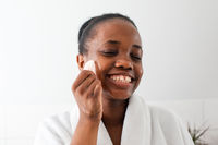 Lovely african girl massaging face with rose quartz gua sha