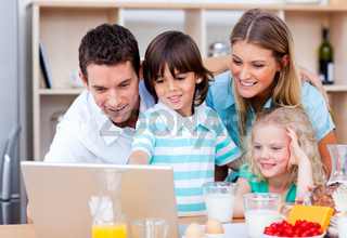 Jolly family using laptop during the breakfast