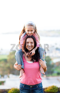 Mother giving daughter piggyback ride