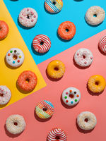 Glazed colorful donuts background, top view