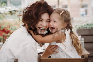 Cute little girl and her beautiful young mom hug each other