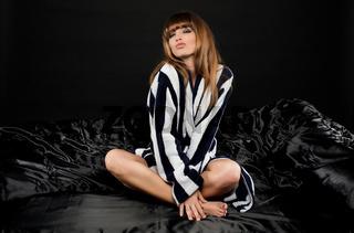 Frau sitzt im Bett mit schwarzer Seidenbettwaesche