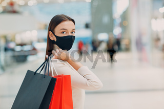 Young adult woman in protective medical face mask carrying paper shopping bags in hands at supermarket