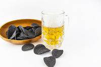 Beer background. Fresh beer and potato chips in a wooden plate. Free space for text.