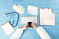 Top view of doctor hand holding smartphone