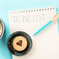 To do list square shot. A notepad with a blue pen and a cookie, shot from above