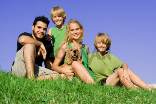 happy family with pet dog in summer