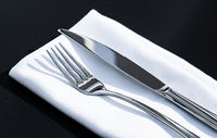 Fork and knife with white napkin on table in luxury restaurant outdoors, fine dining menu for wedding or event and food catering service concept