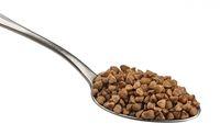 Spoon of buckwheat seeds isolated on white