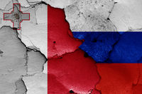 flags of Malta and Russia painted on cracked wall
