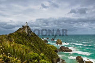 Nugget Point Leuchtturm in dunklen Wolken am Himmel, Catlins, Neuseeland