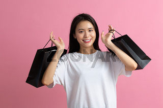 Shopping asian happy woman holding shopping bags on pink background